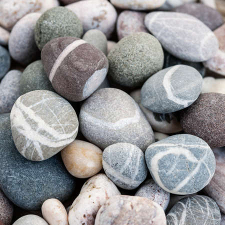 Small round beach pebbles or smooth rocks with various colors and shapes of stones, macro close up. Square format.