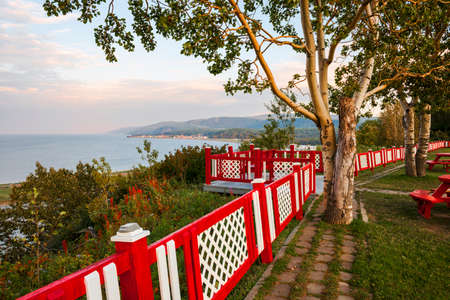 Colorful fence at lookout and picnic area at Cap-de-la-Madeleine historic site on Gaspe peninsula in Quebec, Canada. Фото со стока