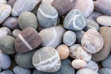 Ronde strand kiezels of gladde rotsen met verschillende kleuren en vormen van stenen close-up Stockfoto