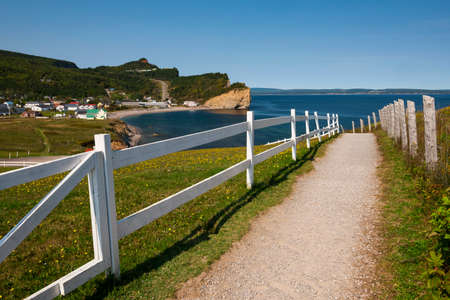 Pedestrian path with white wooden fence leading to view point of Perce Rock and Atlantic ocean coast in Perce, Gaspe peninsula, Quebec, Canada. Фото со стока