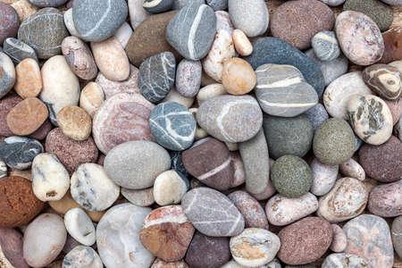 Kleine afgeronde strandkiezels of gladde rotsen met verschillende kleuren en vormen van stenen, bovenaanzicht.