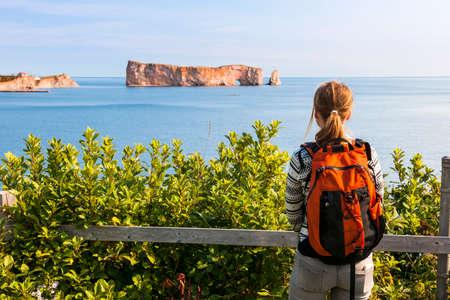 Jonge toeristenvrouw die met rugzak Perce Rock-mening genieten van Gaspe-Schiereiland in Quebec, Canada