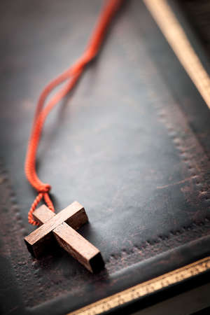Closeup of simple wooden Christian cross necklace on holy Bible with copy space Standard-Bild