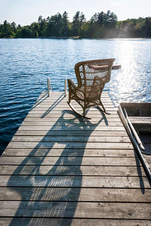Wicker rocking chair on wooden dock in summer at small lake casting long shadow