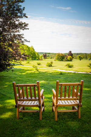 Two wooden chairs on lush green lawn with view of countryside in summer Фото со стока
