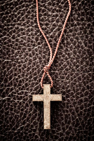 Closeup of simple wooden Christian cross necklace on leather bound holy Bible Standard-Bild