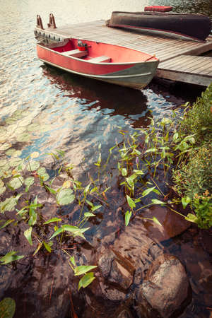 Red boat at wooden dock on lake in cottage country with foreground of rocks and plants Фото со стока