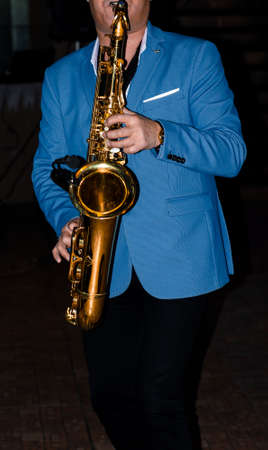 Saxophonist. A musician in a jacket plays a melody on a saxophone. Musical instrument. Jazz.