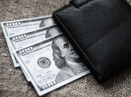 Black and white photo of dollars. American paper banknotes. There are several hundred-dollar bills under black wallet. Cash. Finance. Stock Photo