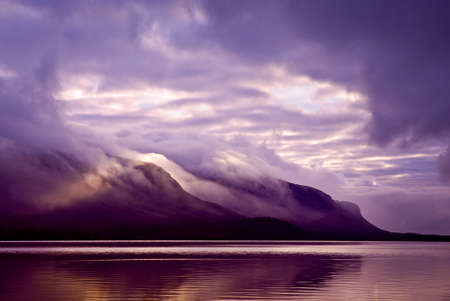 Landscape. Mountains and lake in mist in morning with purple color  photo
