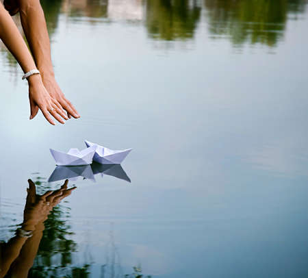 Man and womans hands and two paper boats photo