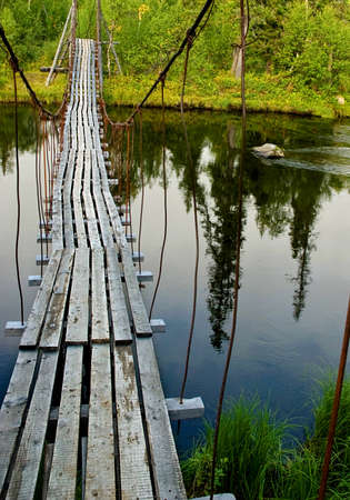 Old suspension walk bridge across river in the forest  photo