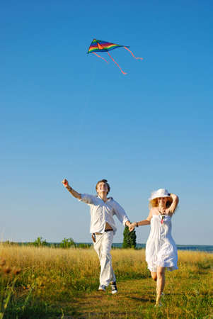 emotional love: Happy young couple flying a kite  Stock Photo