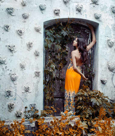 Beautiful young girl in a long dress standing against a wall with a door  photo
