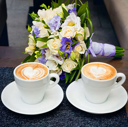 Two cups of coffee on the table, with bridal bouquet.  photo