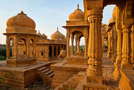 spiritual architecture: The royal cenotaphs of historic rulers, also known as Jaisalmer Chhatris, at Bada Bagh in Jaisalmer made of yellow sandstone at sunset