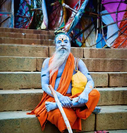 earthly: VARANASI, INDIA - OCT 1: Sadhu sits near the river Ganges, with traditional painted face and body, a sadhu renunciation of all ties that unite with the earthly and material, and for the true values of life, October 1, 2013 in Varanasi, India.