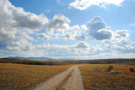 earth road: Strada sterrata, cielo azzurro e nuvole.