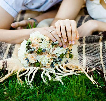 Manos de novia y del novio con los anillos de bodas (enfoque suave)