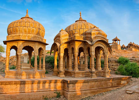 The royal cenotaphs of historic rulers, also known as Jaisalmer Chhatris, at Bada Bagh in Jaisalmer, Rajasthan, India. Cenotaphs made of yellow sandstone at sunset