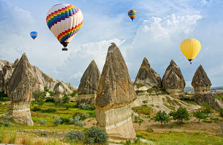 Colorful hot air balloons flying over volcanic cliffs at Cappadocia, Anatolia, Turkey.
