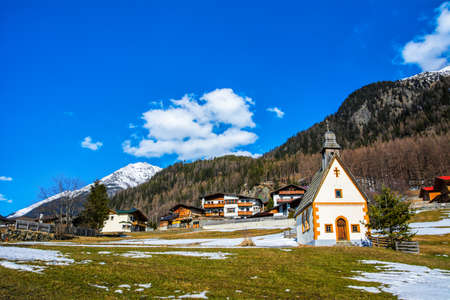 Amazing view of winter wonderland mountain scenery with church in the Alps on a sunny day with blue sky