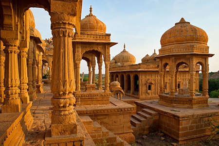 The royal cenotaphs of historic rulers, also known as Jaisalmer Chhatris, at Bada Bagh in Jaisalmer made of yellow sandstone at sunset