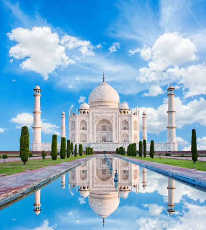 Amazing view on the Taj Mahal in sun light with reflection in water. The Taj Mahal is an ivory-white marble mausoleum on the south bank of the Yamuna river. Agra, Uttar Pradesh, India. Stock Photo