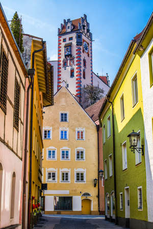 Beautiful street of old houses with the tower of the High Castle, Fussen city, Germany