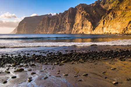 Amazing view from beach in Los Gigantes with high cliffs on the sunset. Location: Los Gigantes, Tenerife, Canary Islands. Artistic picture. Beauty world. Фото со стока