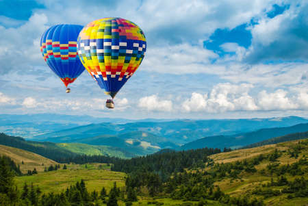 Colorful hot-air balloons flying over the mountains. Artistic picture. Beauty world. Фото со стока