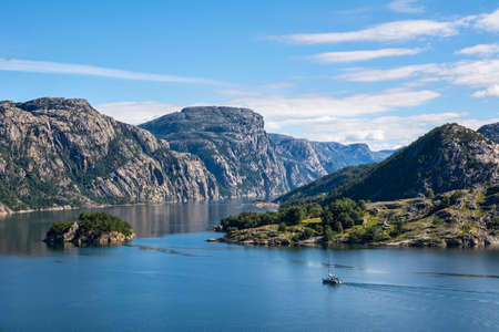 Fantastic nature landscape view of the fjord, mountains and sailing vessel. Location: Lysefjorden, Scandinavian Mountains, Norway, Europe. Artistic picture. Beauty world.  Фото со стока