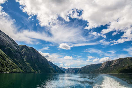 Amazing nature view with beautiful clouds above the fjord. Location: Lysefjorden, Norway, Europe. Artistic picture. Beauty world.  Фото со стока
