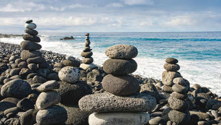 Stack of zen stones over water and blue sky. Shallow depth of field. Canary Islands