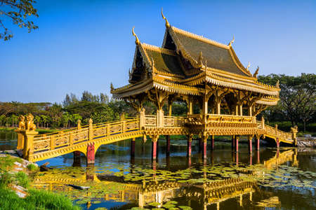 Amazing view of beautiful Golden Bridge and Pavilion of the Enlightened with reflection in the water. Location: Ancient City Park, Muang Boran, Samut Prakan province,  Bangkok, Thailand. Artistic picture. Beauty world.