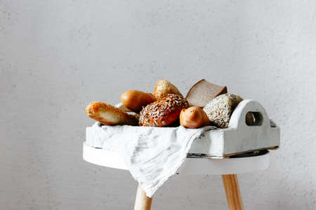 Different types of bread on a tray in a light key