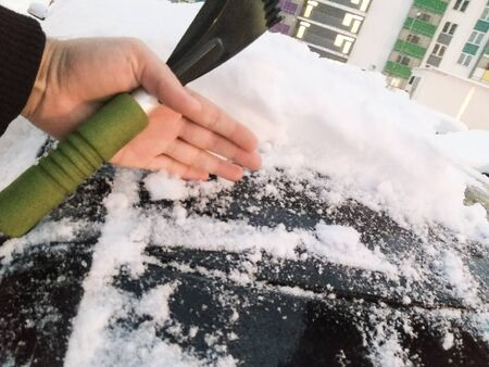 cleans a snow scraper in the hands of a car