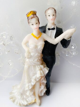 statuette of a bride and groom on a light background