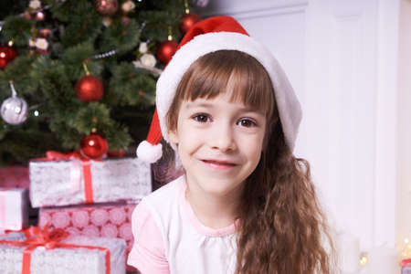 Cute girl. Christmas background. Beautiful gift