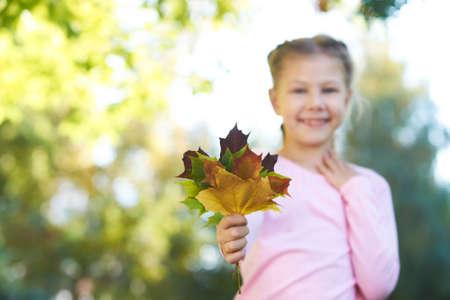 Autumn portrait. Little girl. Child. Sheet. Nature.