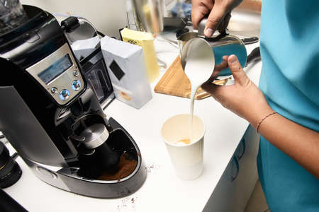Preparation of drink. Coffee with milk. Blue apron. Stock Photo