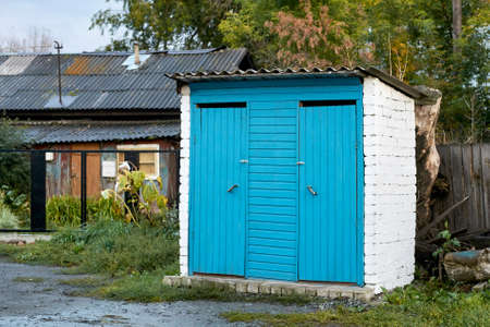 Street toilet. Overcast weather. Country buildings. Blue paint.