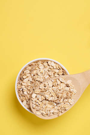 Healthy eating. Oat flakes. Wooden spoon. Yellow background.