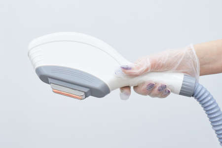 Modern equipment. Laser hair removal. Light background. Personal care Stock Photo