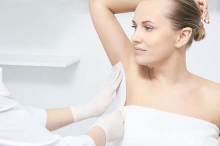 Unwanted hair wax epilation. Young Woman. cosmetology salon treatment procedure. Home waxing.