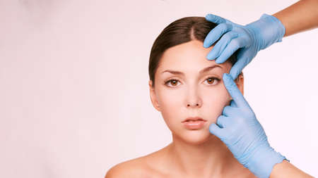 Aesthetic skin consultation. Patient and doctor gloves. Cosmetology treatment. Archivio Fotografico - 113610048