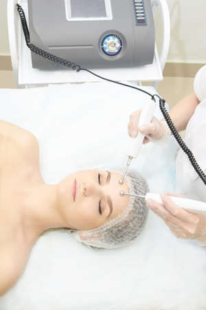 Facial micro current cosmetology procedure. Beauty technology treatment. Woman face therapy. Stock Photo