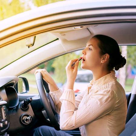 Girl applying make up. Dangerous risky driver. Imagens