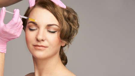 Inyección con aguja facial. Procedimiento de cosmetología de mujer joven. Guantes de doctor. Frente. Foto de archivo