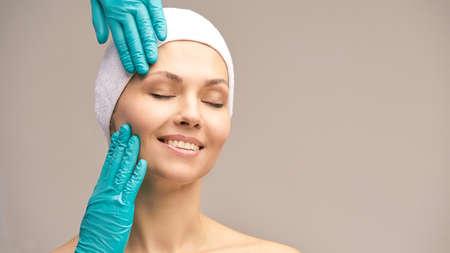 Tratamiento derma rejuvenecedor. Cirugía facial de cosmetología. Examen antiarrugas. Manos de guante de mujer y médico.